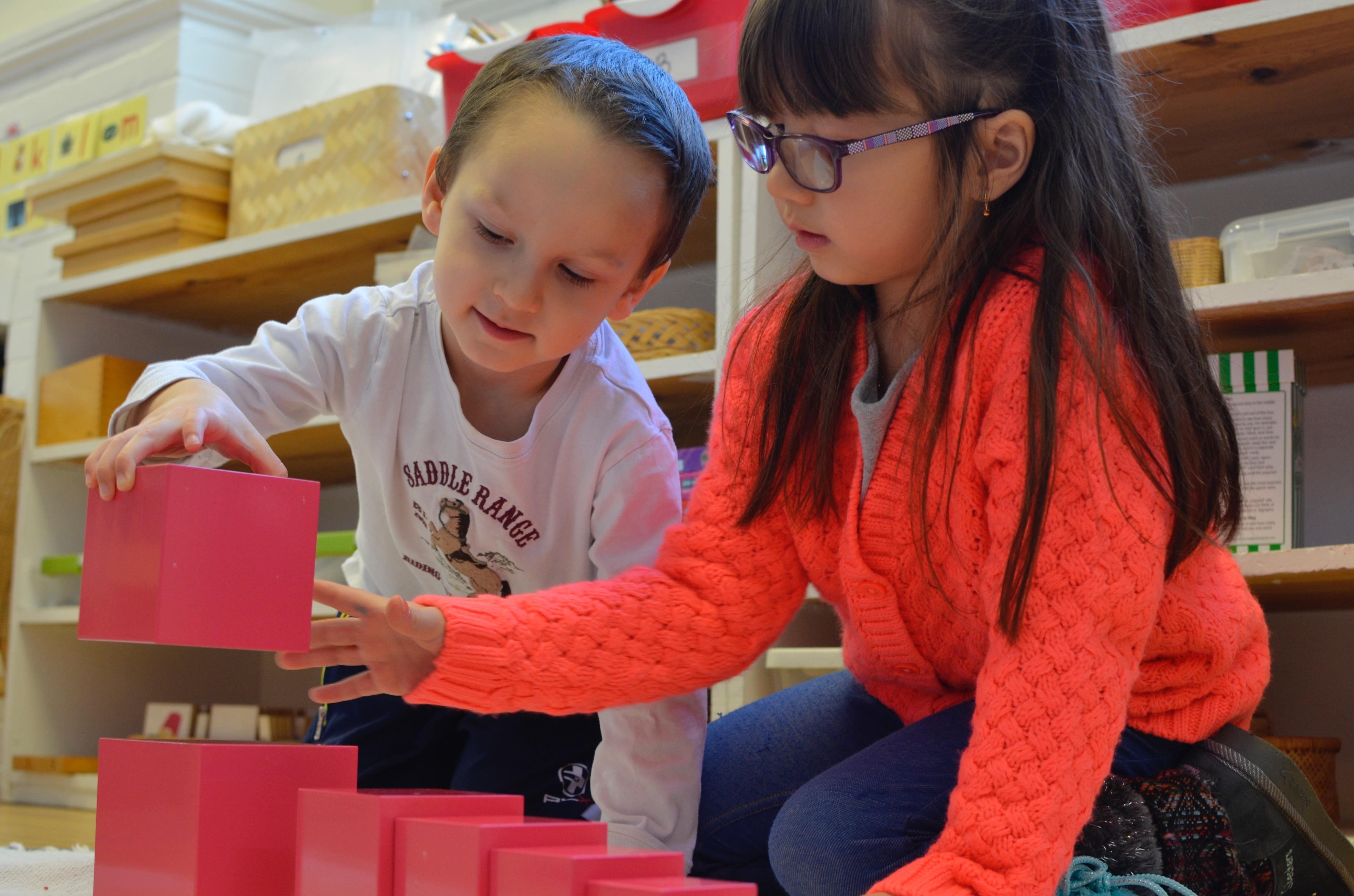 Primary student guiding younger student on building the pink tower