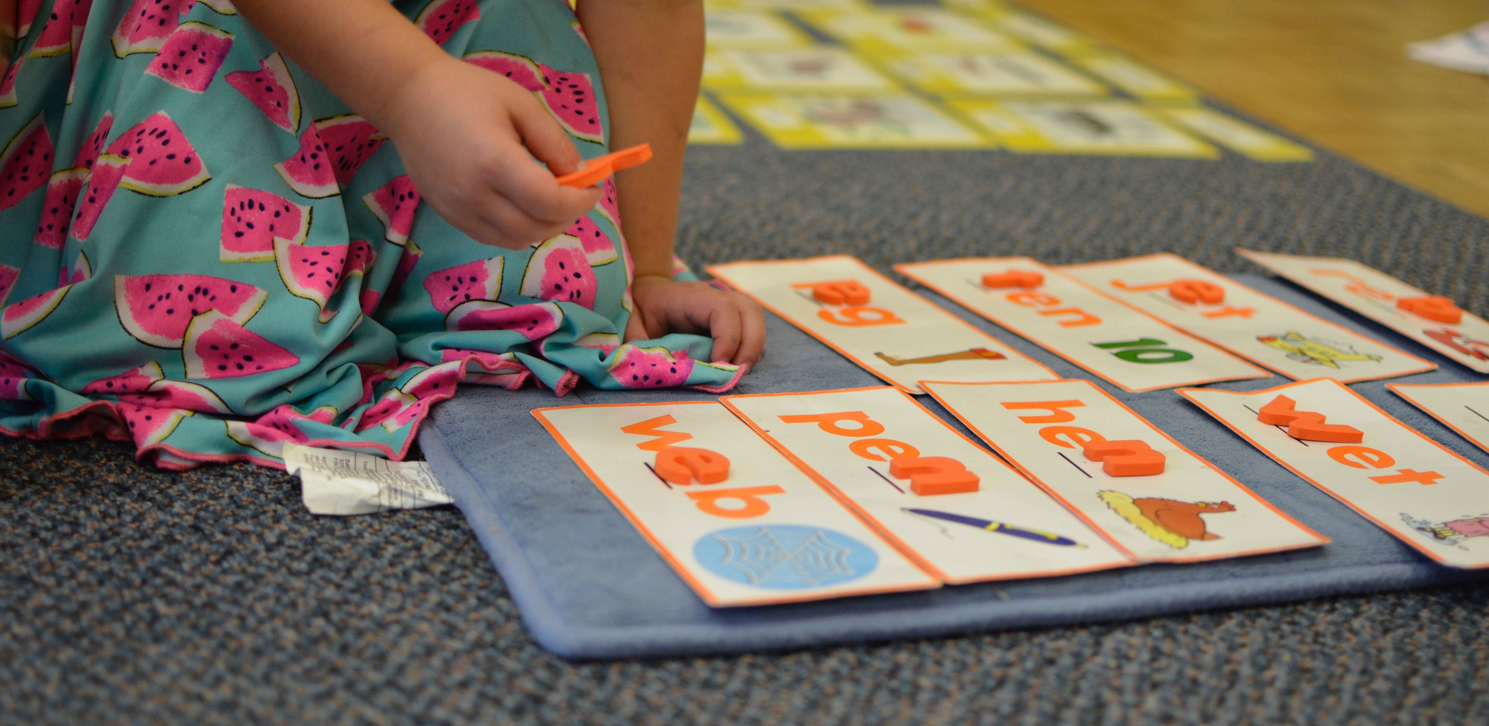 A toddler using hands-on letters to spell out three letter words.