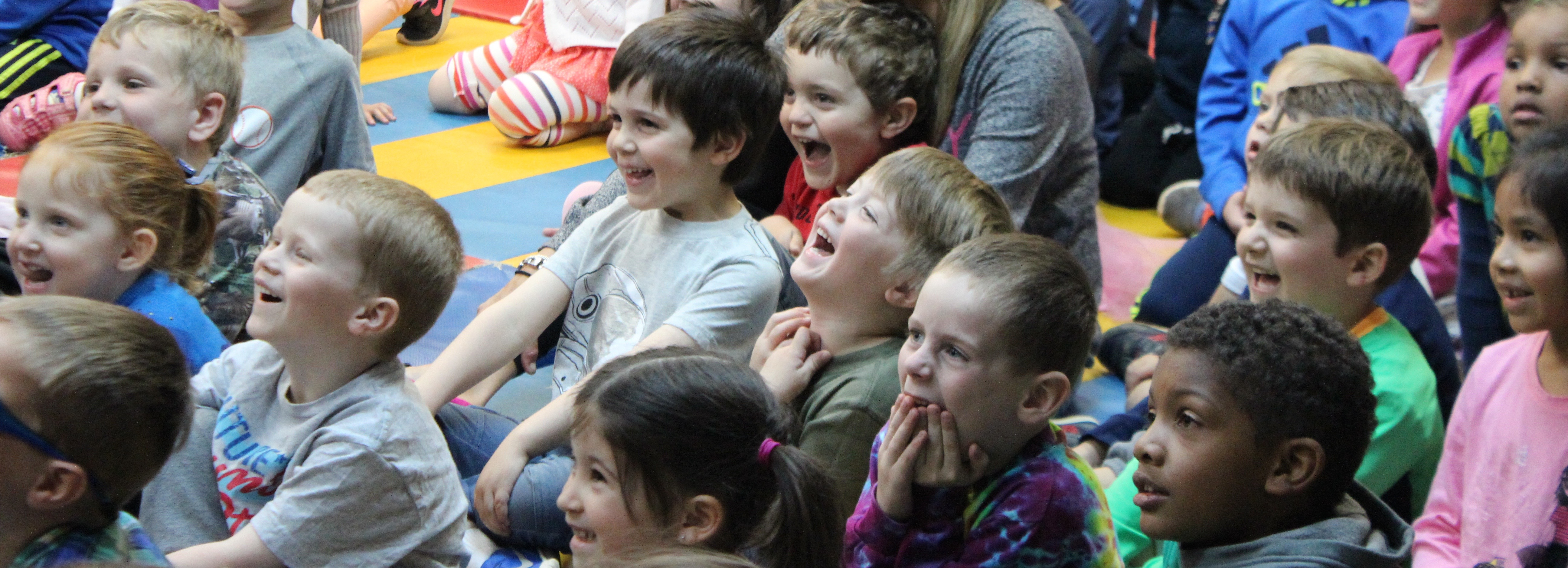 3-6 year old children laughing as they watch a performance.